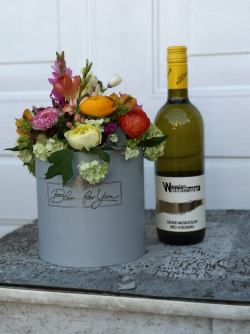 Blumenbox und Wein als Geschenk