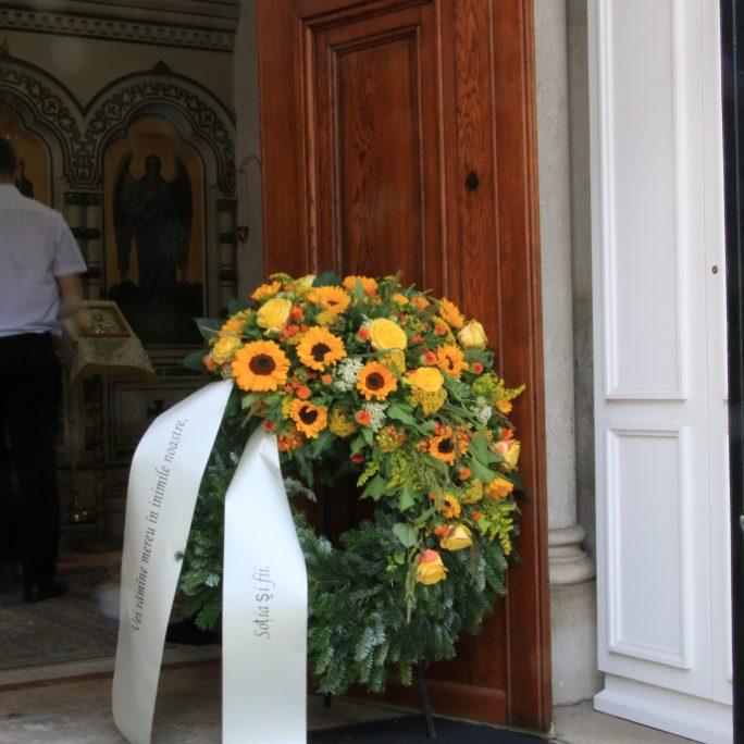 Trauerkranz mit Sonnenblumen und weiteren Saisonblüten in gelb