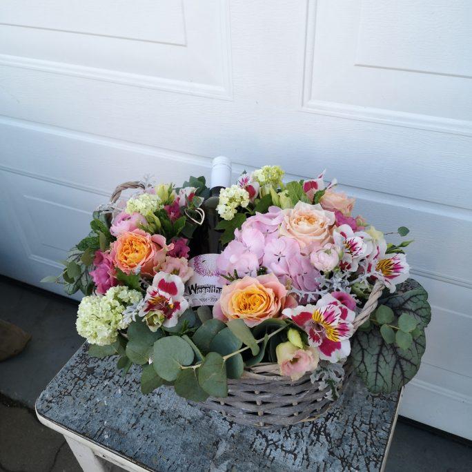 Blumengesteck im Korb samt wein